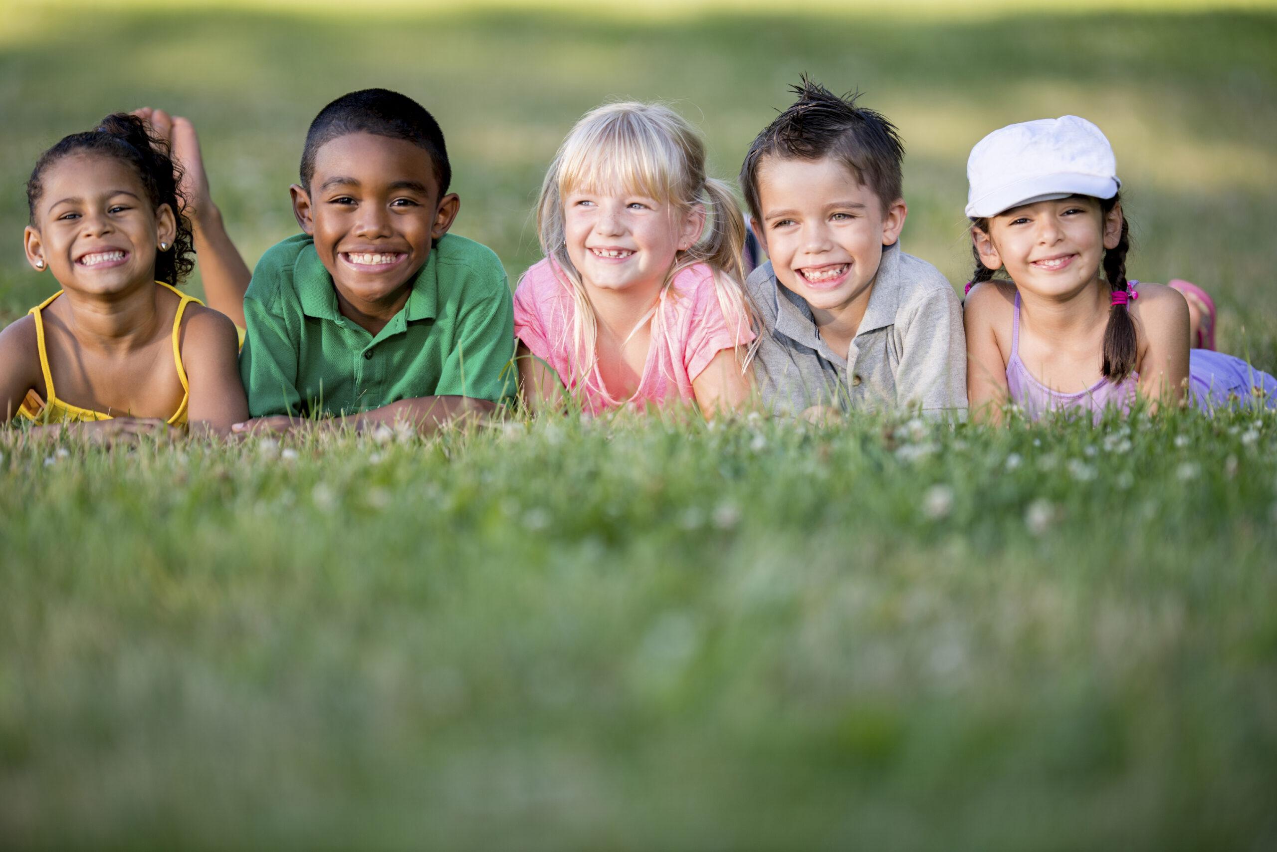 Kinder liegen auf dem Rasen und lachen freundlich in die Kamera