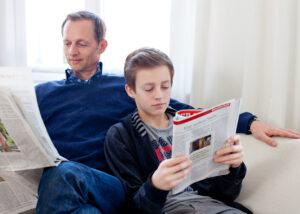 Vater und Sohn sitzen auf der Couch und lesen Zeitung