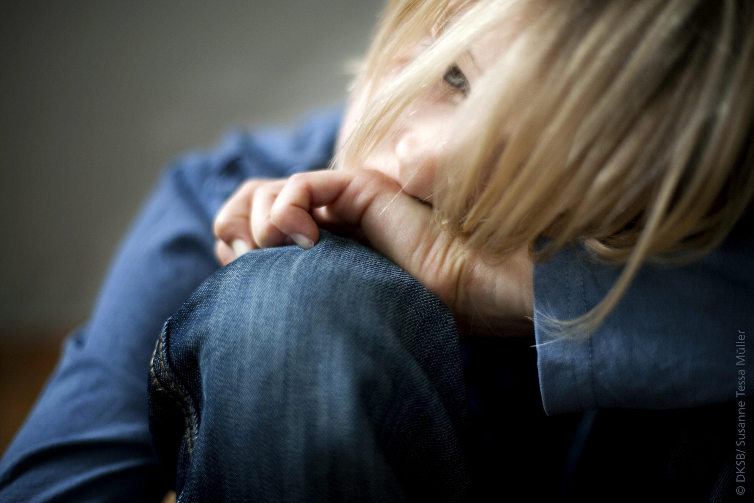 Ein Kind sitzt und denkt nach