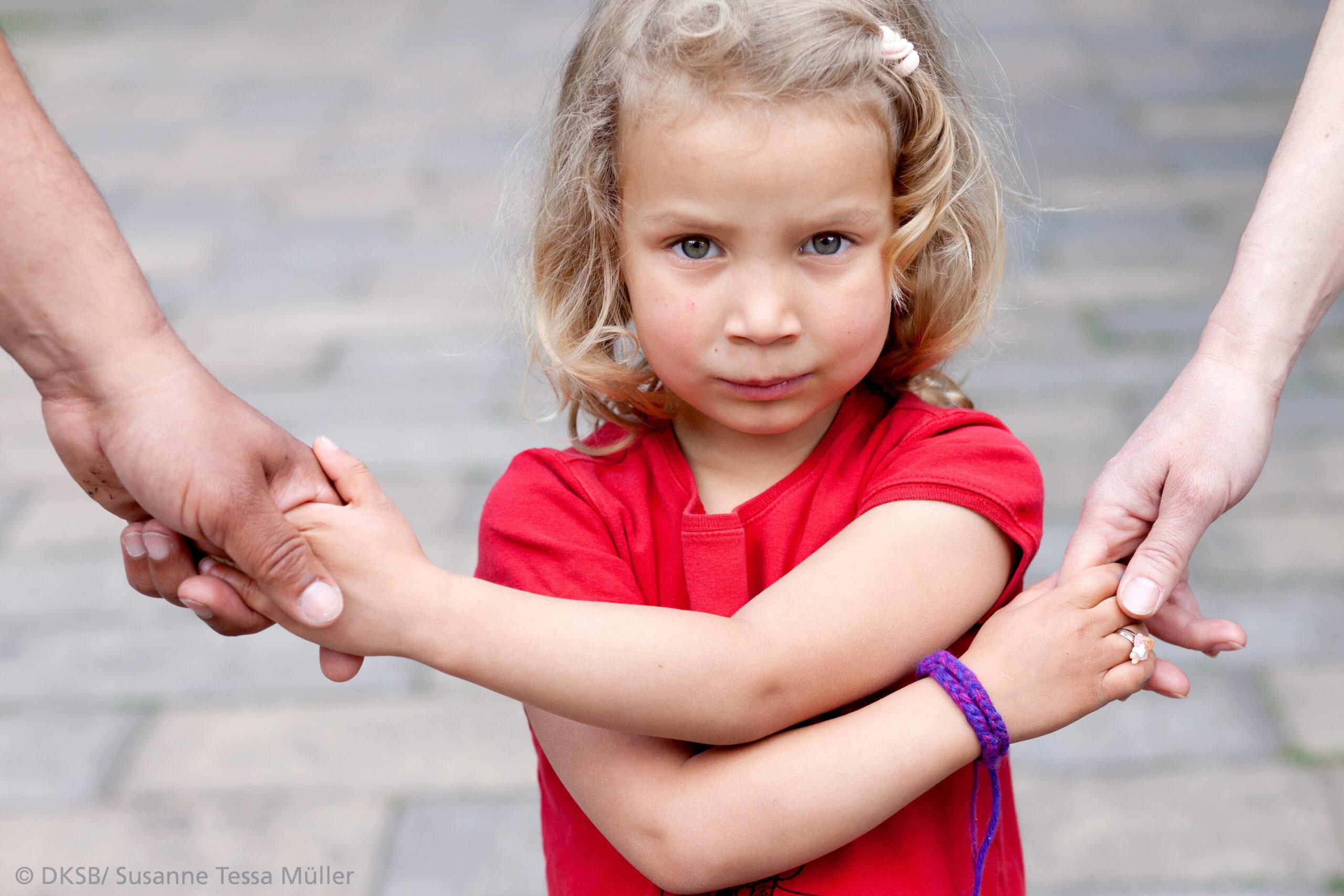 ein Kind hält die Hände von erwachsenen fest