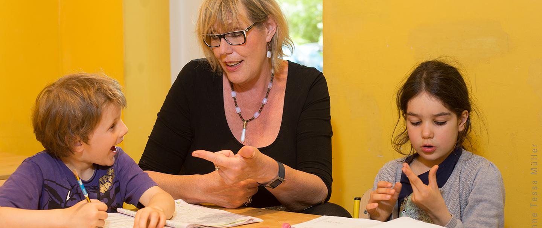 Eine Frau sitzt mit zwei Kindern am Tisch