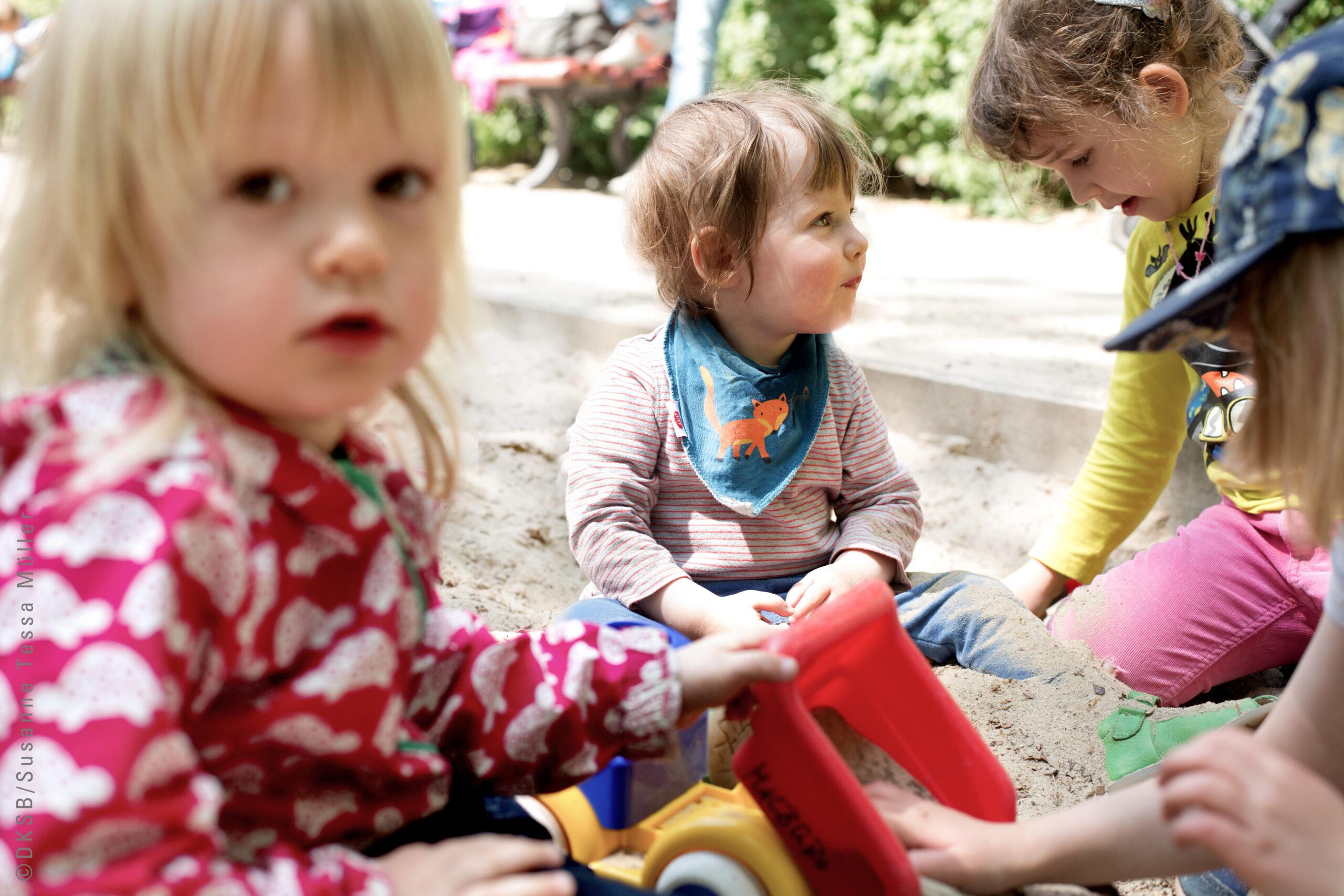 Kinder spielen auf dem Sand