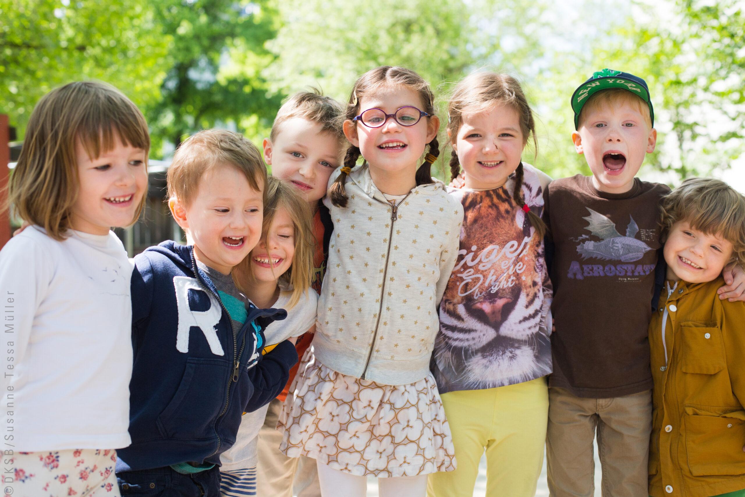 Kinder halten sich fest und lachen in die Kamera