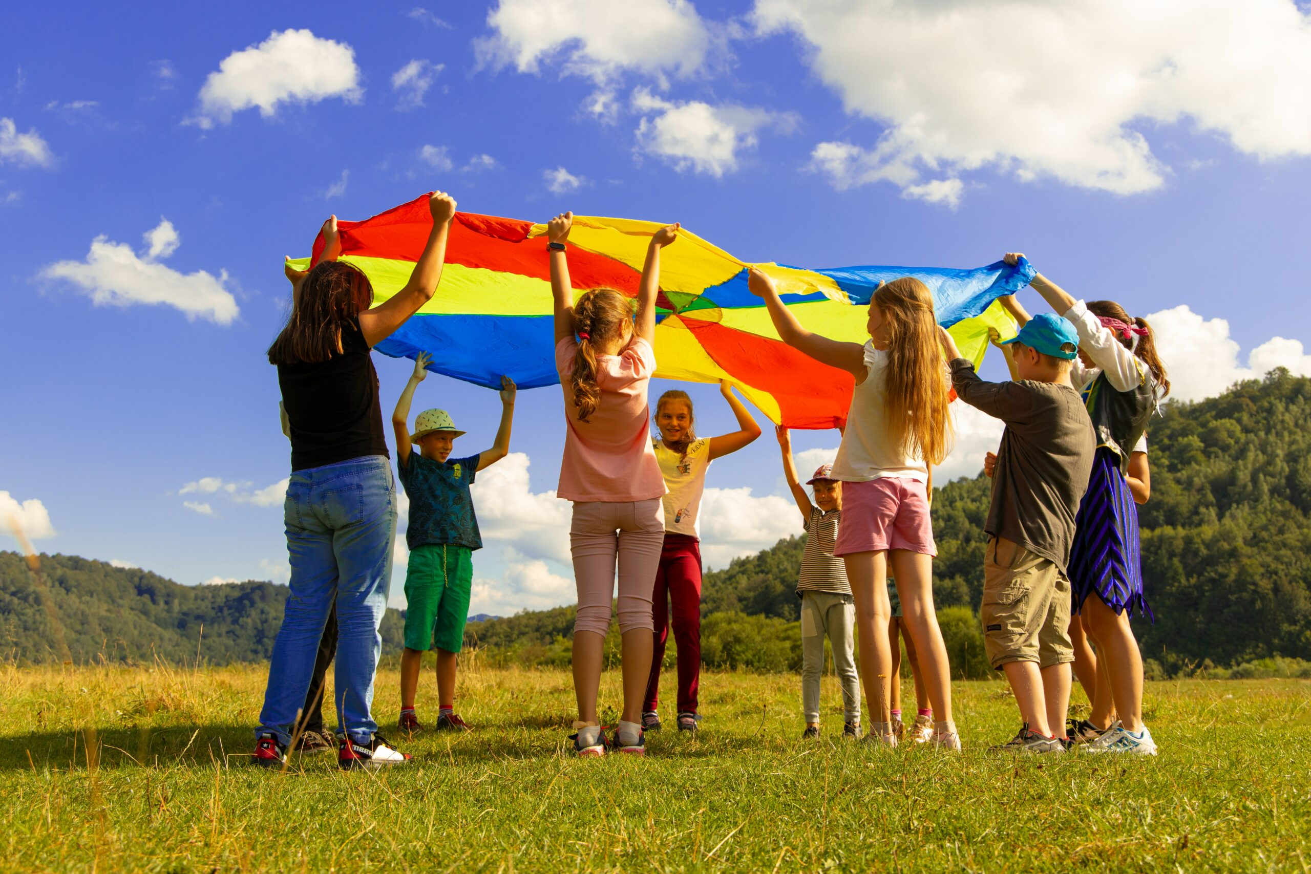 Kinder heben eine Plane in die Luft