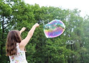 Ein Kind macht eine große Seifenblase